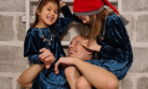 Man holding two girls on his shoulders and laughing.