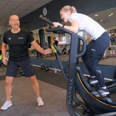 Man shouting at a woman on a treadmill.