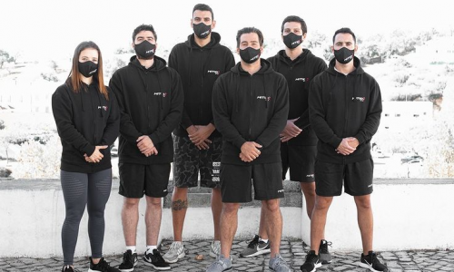 Six men and women dressed in black wearing face covers.